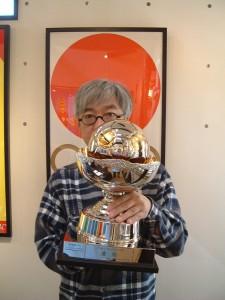 ITサッカーリーグ・優勝トロフィーを持つポスターアーティストの秋山孝